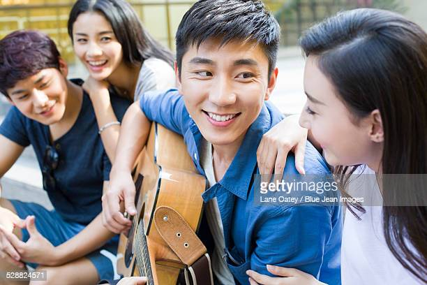 Young man playing guitar with his friends