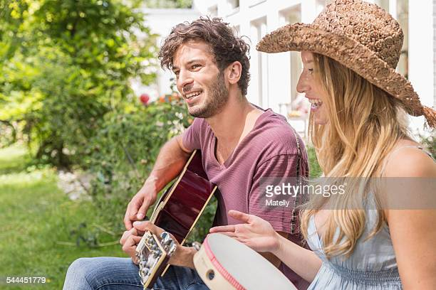 young man playing guitar, woman with tambourine - tambourine stock photos and pictures