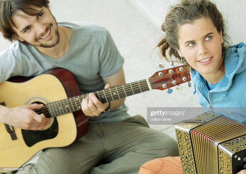 Young man playing guitar, young woman playing accordion : Stockfoto