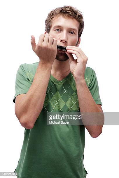 Young man playing harmonica, portrait
