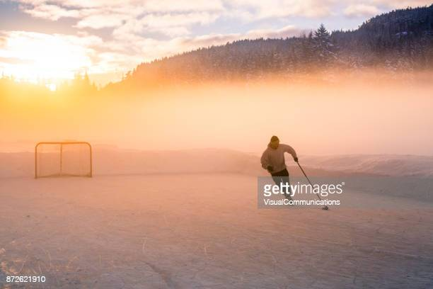 Young man playing hockey on frozen lake.