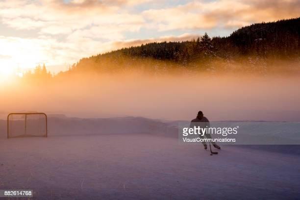 Young man playing hockey on frozen lake.