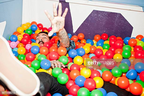 Young man playing in a ball pit