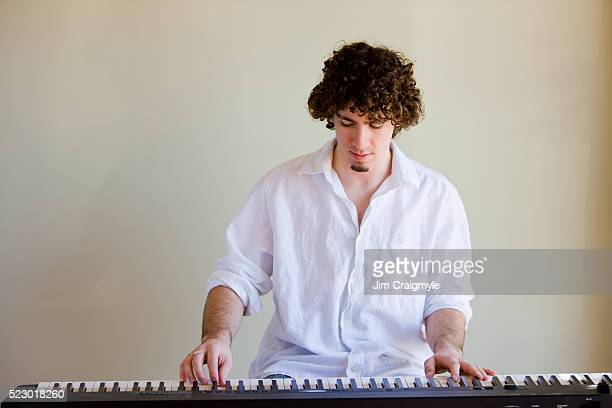 young man playing keyboard - keyboard player stock photos and pictures