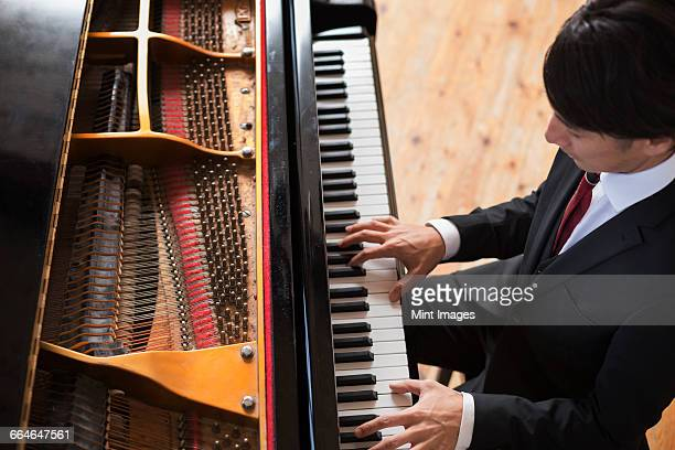 young man playing on a grand piano in a rehearsal studio. - stringed instrument stock pictures, royalty-free photos & images