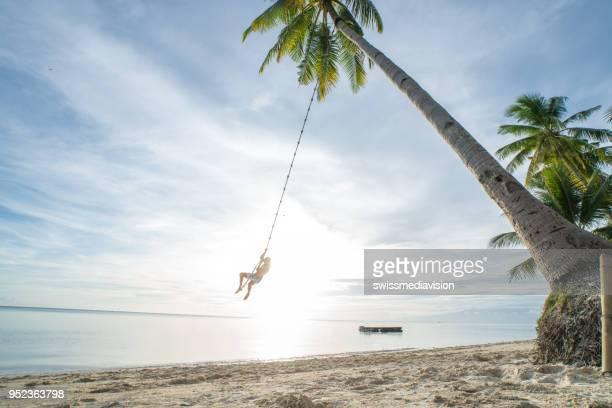 jeune homme jouant sur la plage, corde de la balançoire sur palmier - un seul homme photos et images de collection