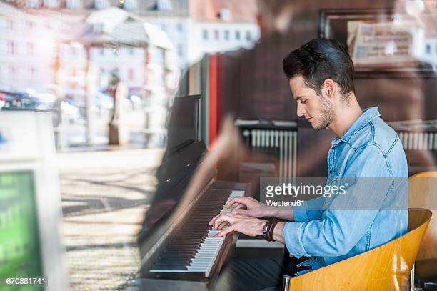 young man playing piano in a cafe - keyboard player stock pictures, royalty-free photos & images