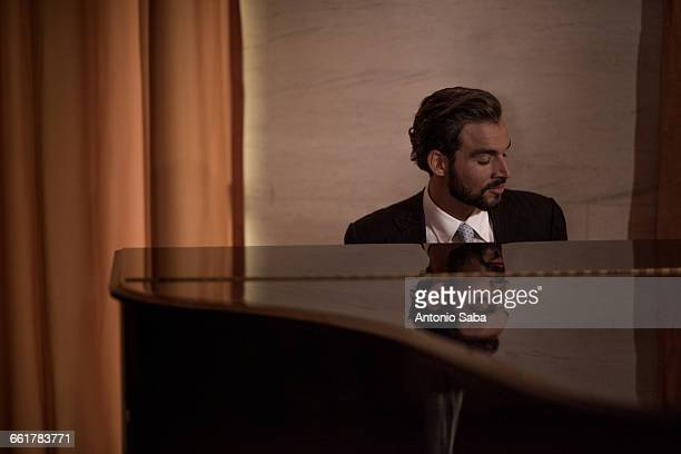 young man playing piano in bar at night - pianist front stock pictures, royalty-free photos & images