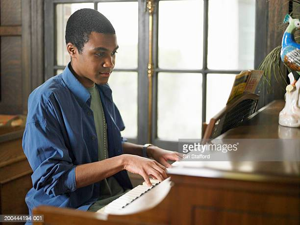 young man playing piano in house - piano player stock photos and pictures