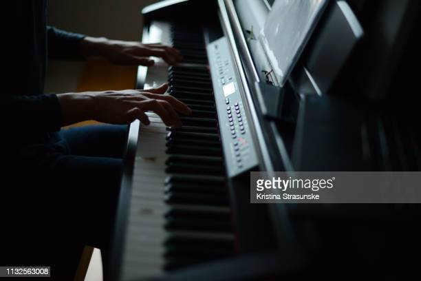 young man playing piano - kristina strasunske stock photos and pictures