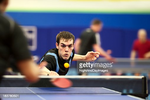 Young man playing ping pong with red racket