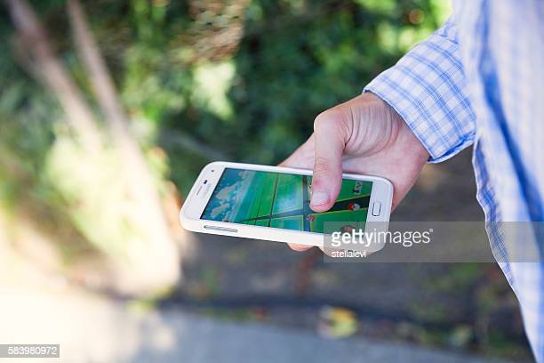 Young man playing Pokémon Go on his smartphone