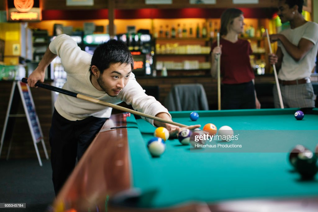 Young Man Playing Pool With Friends : ストックフォト