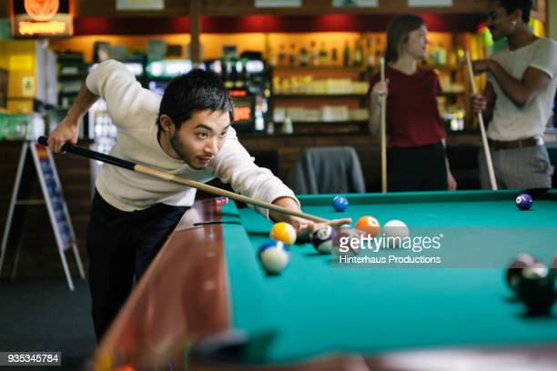young man playing pool with friends - poolbillard billard stock-fotos und bilder