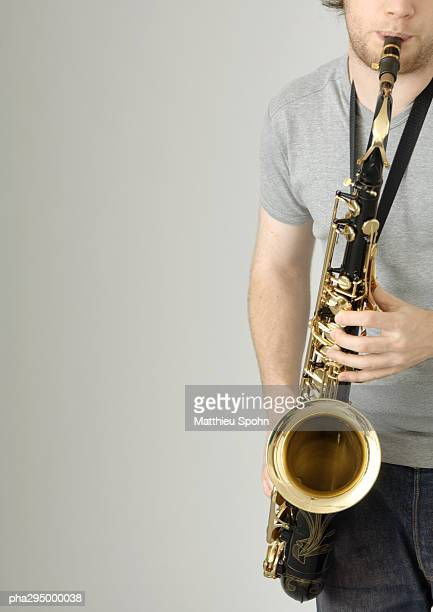Young man playing saxophone, partial view