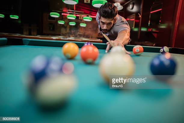 Young man playing snooker in a pub.