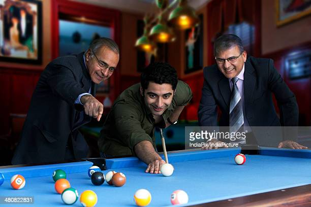 young man playing snooker while businessman pointing at ball in club - old men playing pool stock pictures, royalty-free photos & images