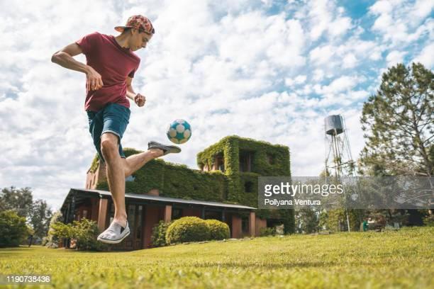 joven jugando al fútbol en la casa de campo - truco fotografías e imágenes de stock