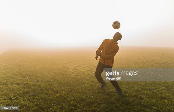 Young man playing soccer on meadow in the evening
