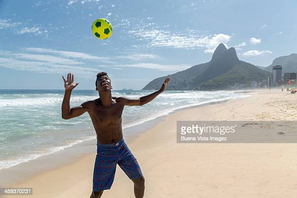 Young man playing soccer on the beach