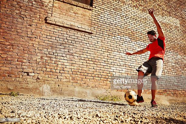 Young man playing soccer on wasteland