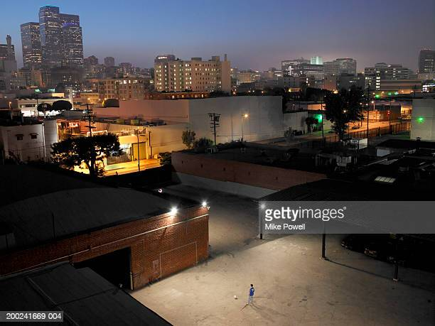 Young man playing soccer outside warehouse, elevated view
