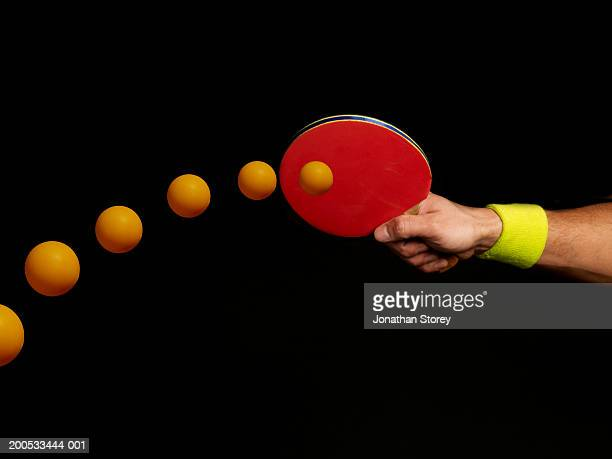 Young man playing table tennis, close-up of hand, (digital composite)
