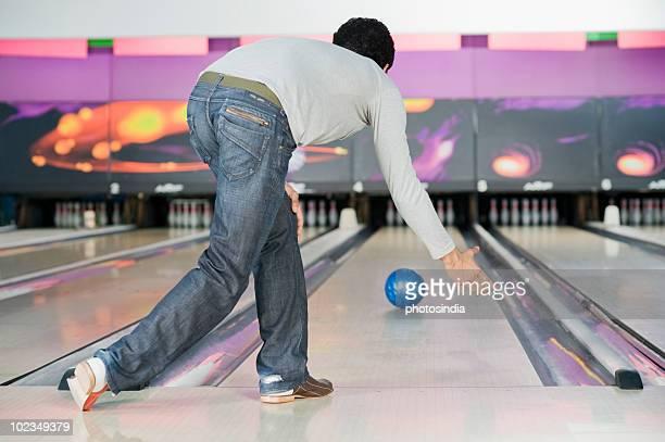 Young man playing ten pin bowling