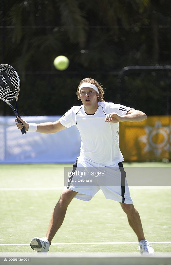 Young man playing tennis on outdoor court : Foto stock