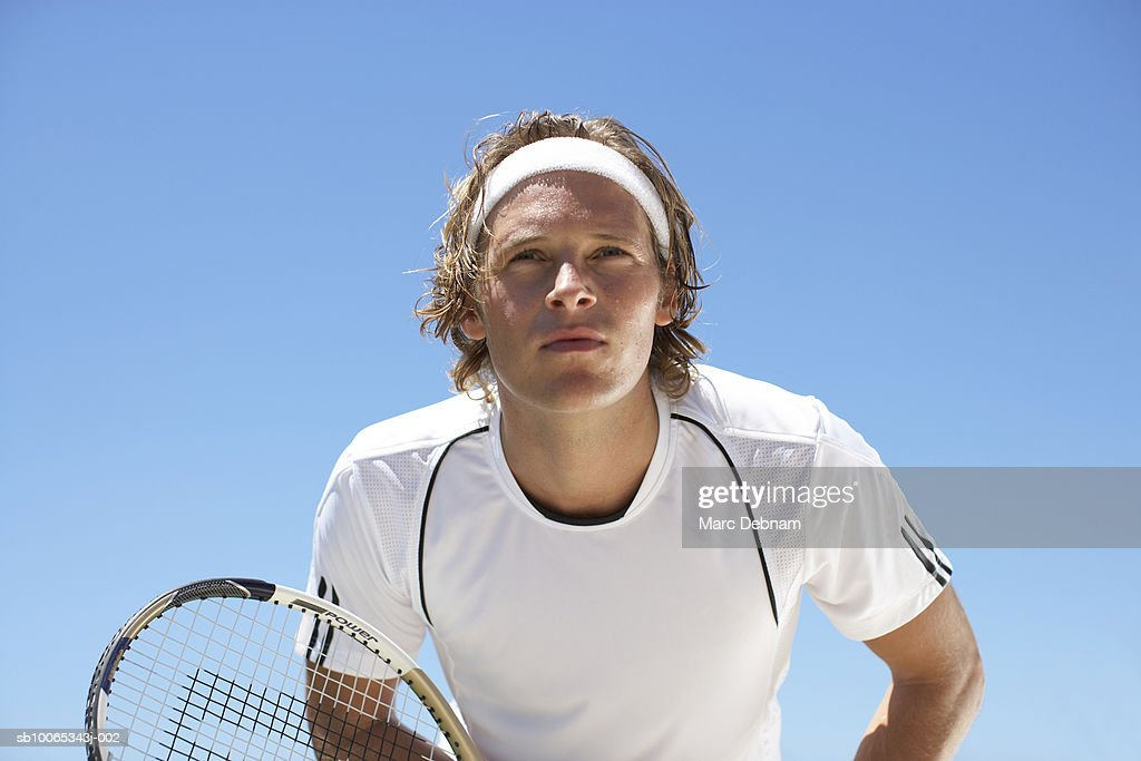 Young man playing tennis outdoors : Foto stock