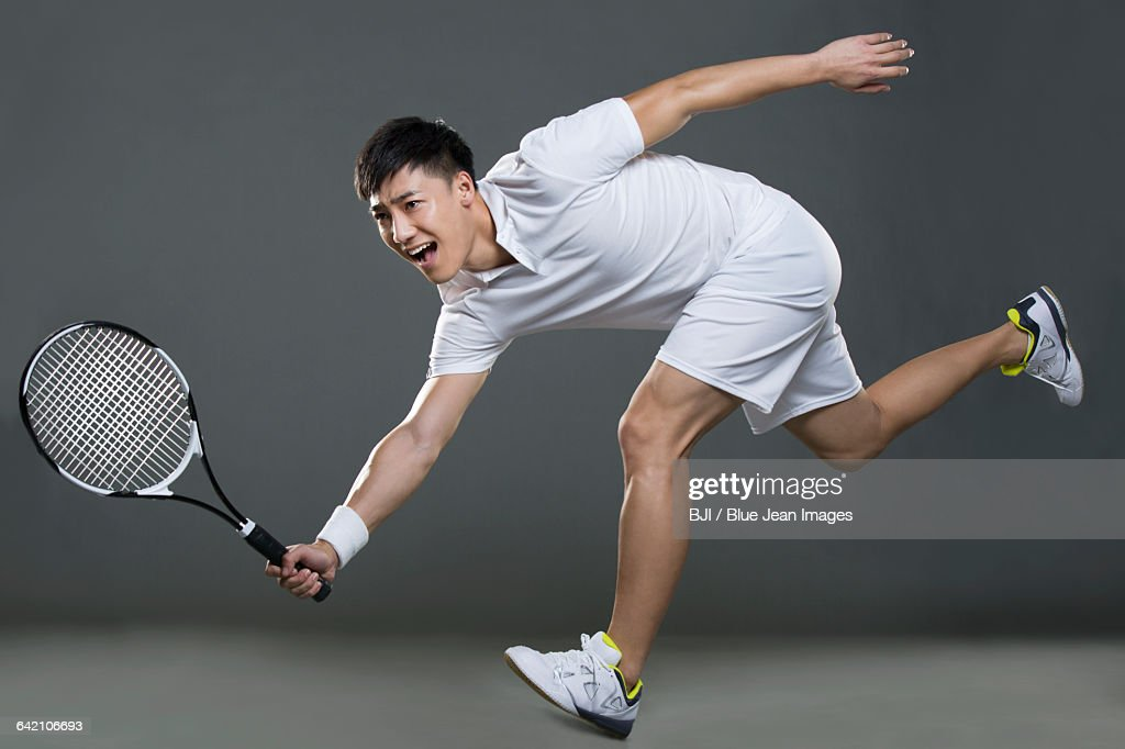Young man playing tennis : ストックフォト