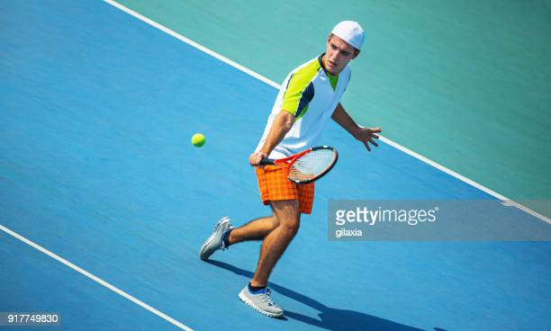 young man playing tennis. - hitting stock pictures, royalty-free photos & images