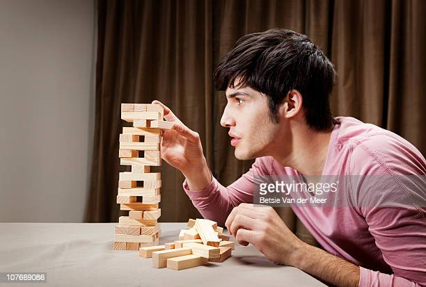 young man playing tension tower game. - newpremiumuk stock pictures, royalty-free photos & images