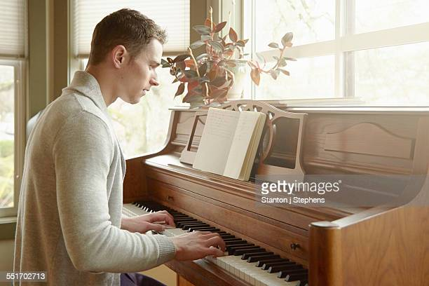 young man playing the piano in living room - keyboard player stock photos and pictures