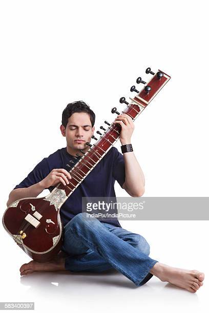 Young man playing the sitar
