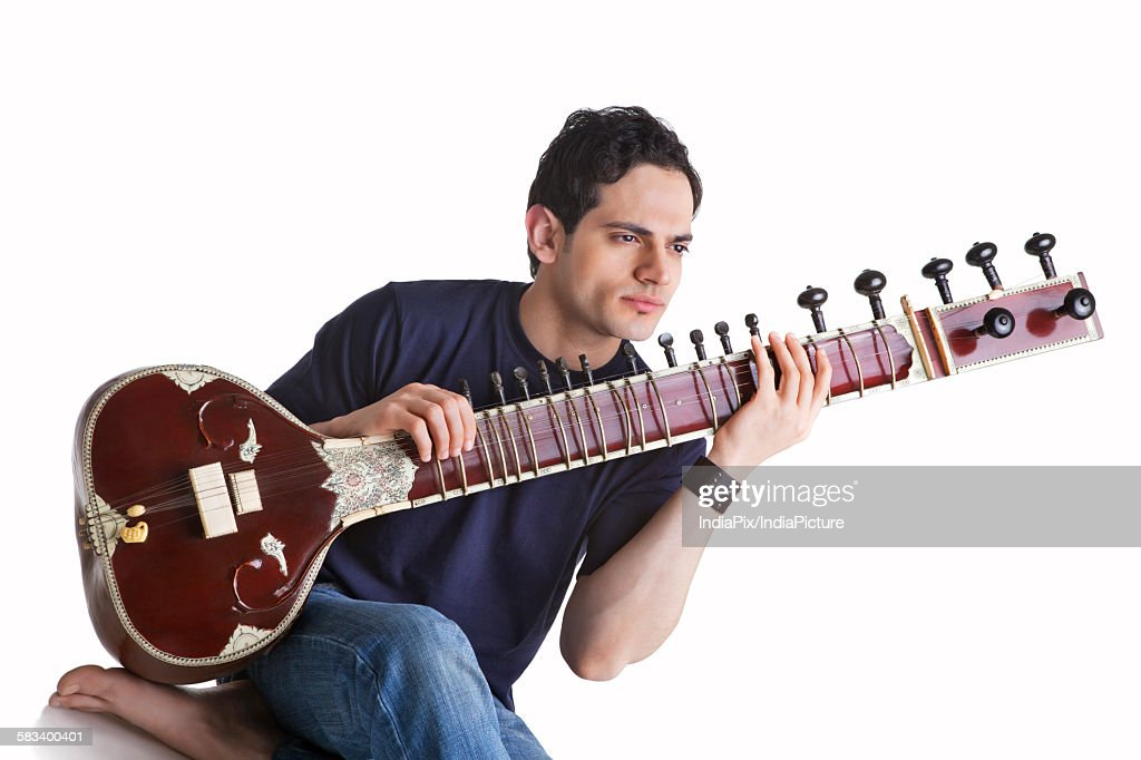 Young man playing the sitar : Stock Photo