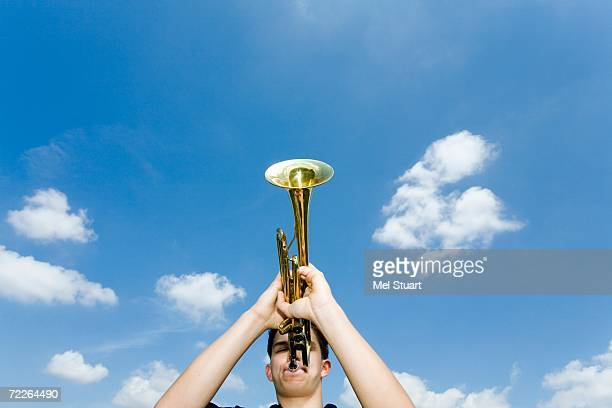 young man playing trumpet, low angle view - トランペット奏者 ストックフォトと画像