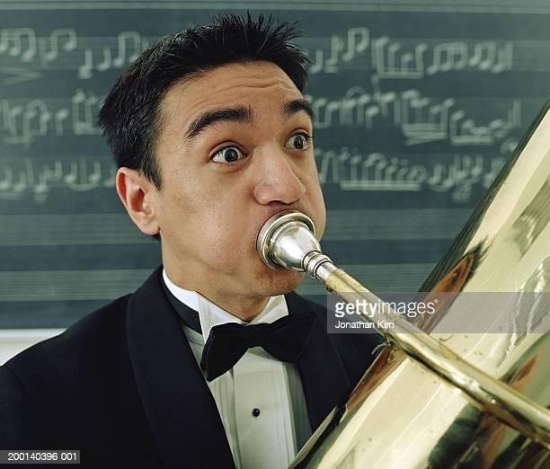 Young man playing tuba, close-up