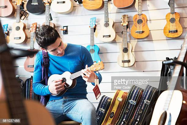 Young man playing ukulele in shop