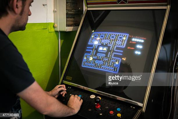 Young man playing vintage arcade videogame