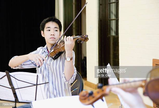 young man playing violin, close-up - classical musician stock pictures, royalty-free photos & images