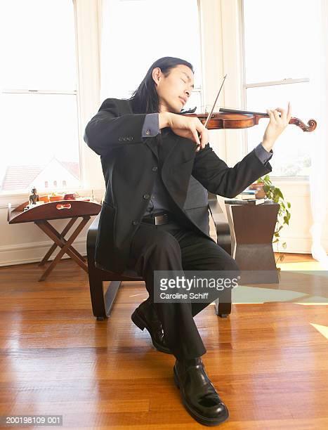 Young man playing violin, eyes closed
