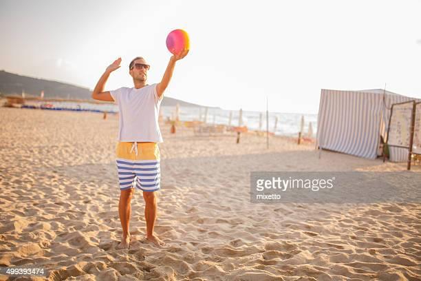 junger mann spielen volleyball am strand - strand volleyball der männer stock-fotos und bilder