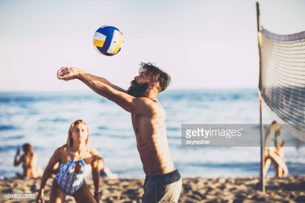 young man playing volleyball with friends on the beach. - beach volleyball stock pictures, royalty-free photos & images