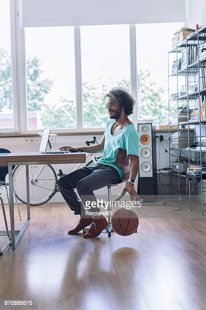 young man playing with basketball in office - dribbling sports stock pictures, royalty-free photos & images