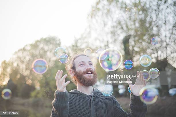 Young man playing with bubbles