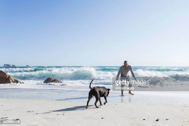 Young man playing with his dog at the beach.