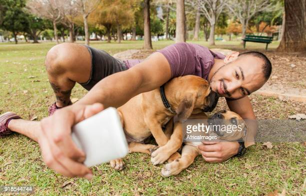Young man playing with his puppies and taking selfies.