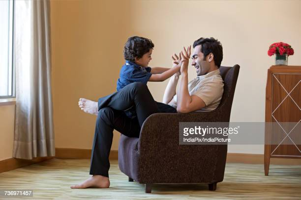 Young man playing with his son sitting on armchair