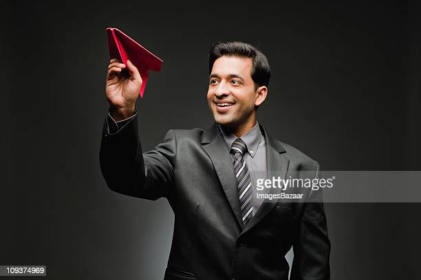 young man playing with paper plane - holding aloft stock pictures, royalty-free photos & images